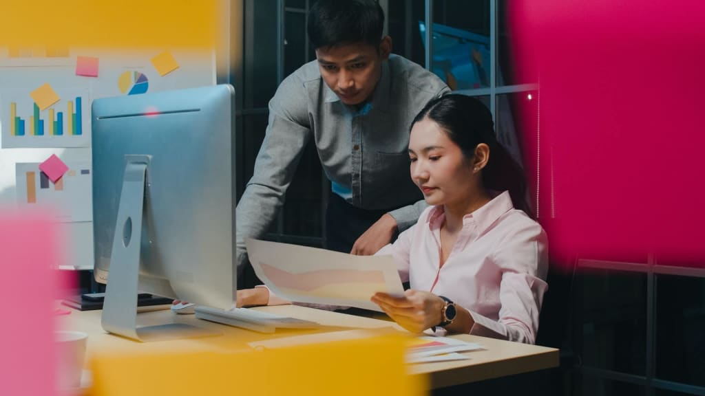 Asia businessman and businesswoman in small modern night office.