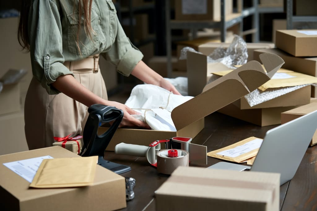Female online store business owner packing ecommerce shipping box.