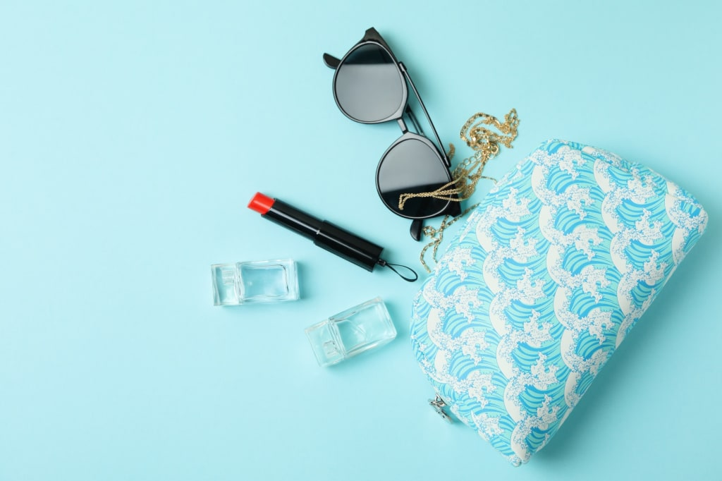 Cosmetic bag and female accessories on blue background