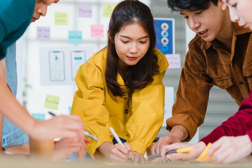 Asian businessmen and businesswomen meeting brainstorming ideas about creative web design planning