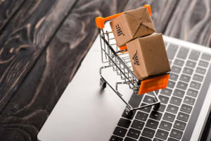 toy boxes in small shopping cart on laptop, e-commerce concept