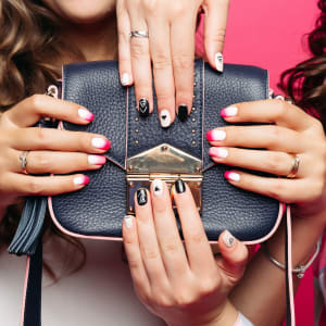 Women holding leather handbag with trendy manicure