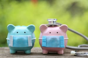 Piggy bank wearing medical mask and stethoscope