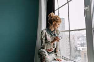 Woman drinking chamomile tea in pajamas