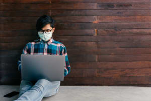 A man working on a laptop with a mask on