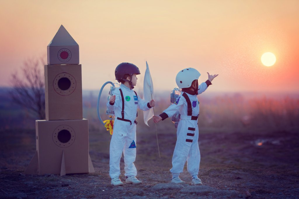 Two adorable children,boy brothers,playing in park on sunset,dressed like astronauts,imagining they are flying on the moon