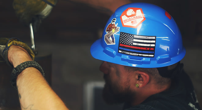 Construction worker wearing a blue hard hat with stickers ...