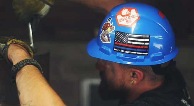 Construction worker wearing a blue hard hat with stickers