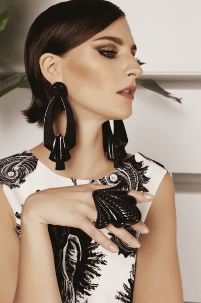 Model wearing black 3d printed earrings