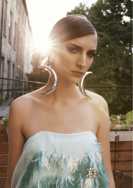 Model wearing a crescen moon earrings