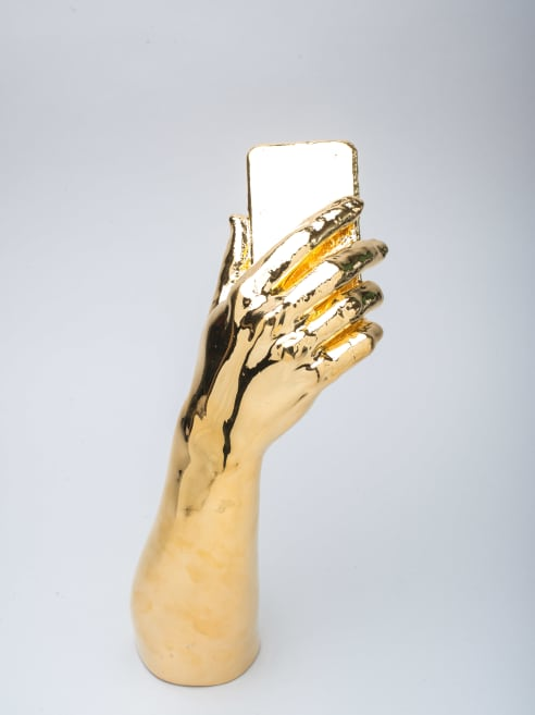Metal plated golden hand holding a phone