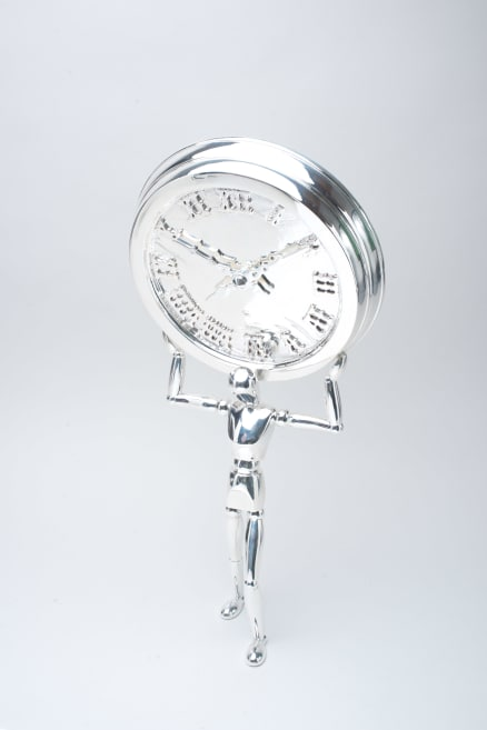 Metal plated sculpture holding a clock