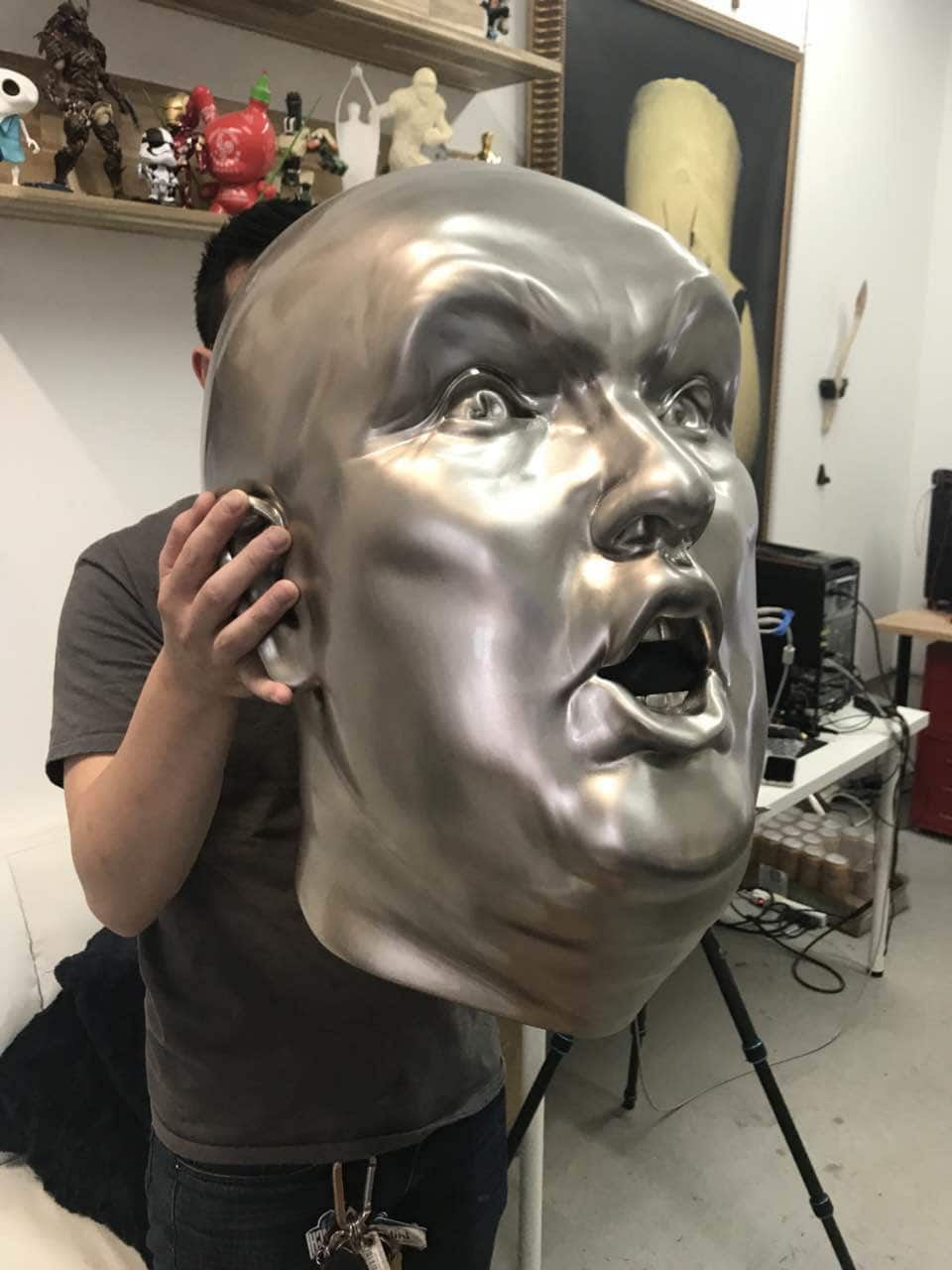 man holding a metal plated donald trump's head