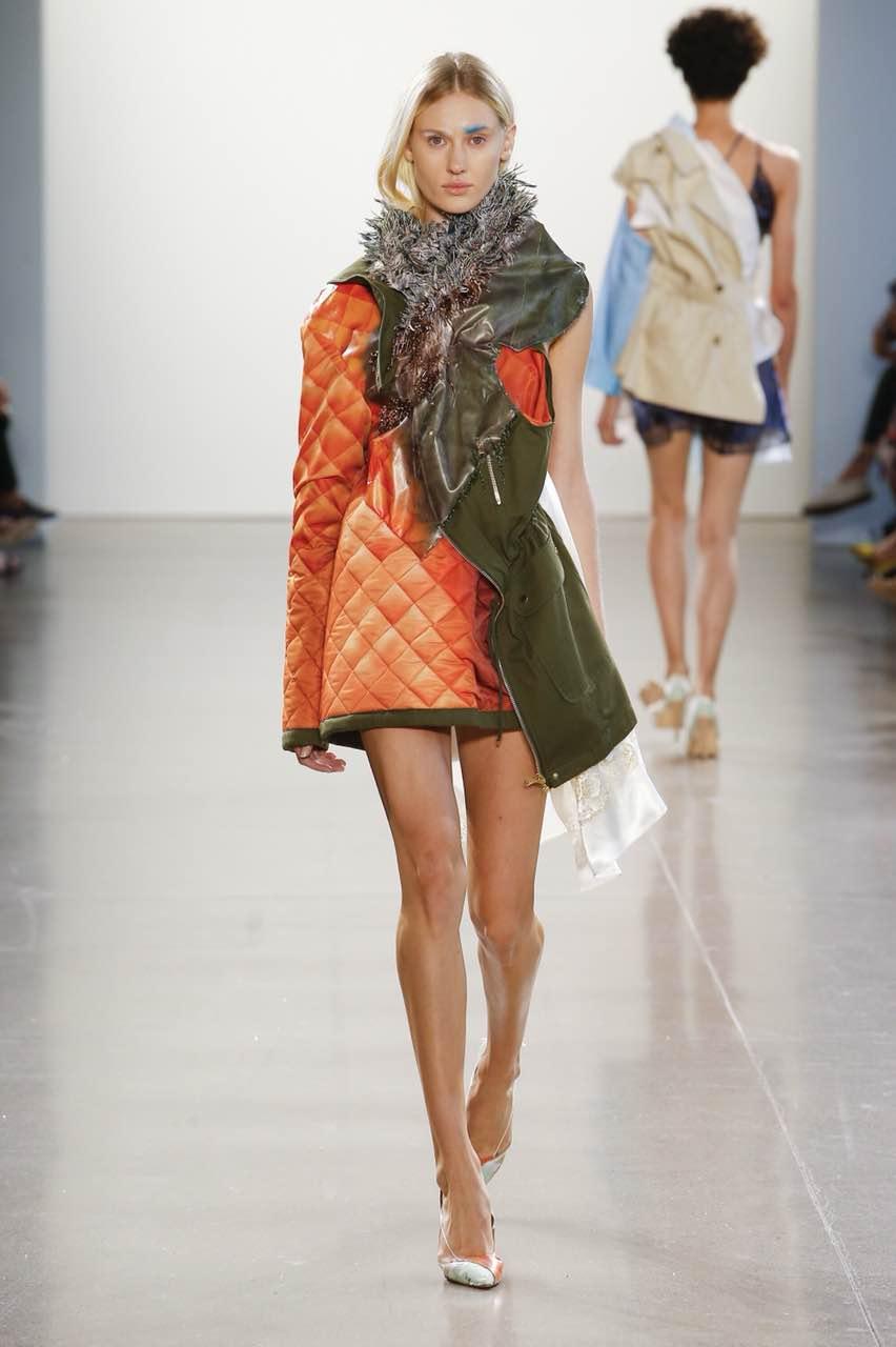 woman wearing orange jacket walking on runway