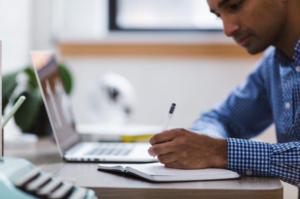 Colaborador escrevendo em um bloco de notas personalizado da sua empresa.