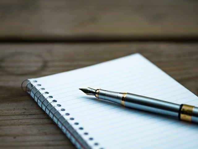 caneta e caderninho em cima de uma mesa, para definir diferentes ideias de encadernação