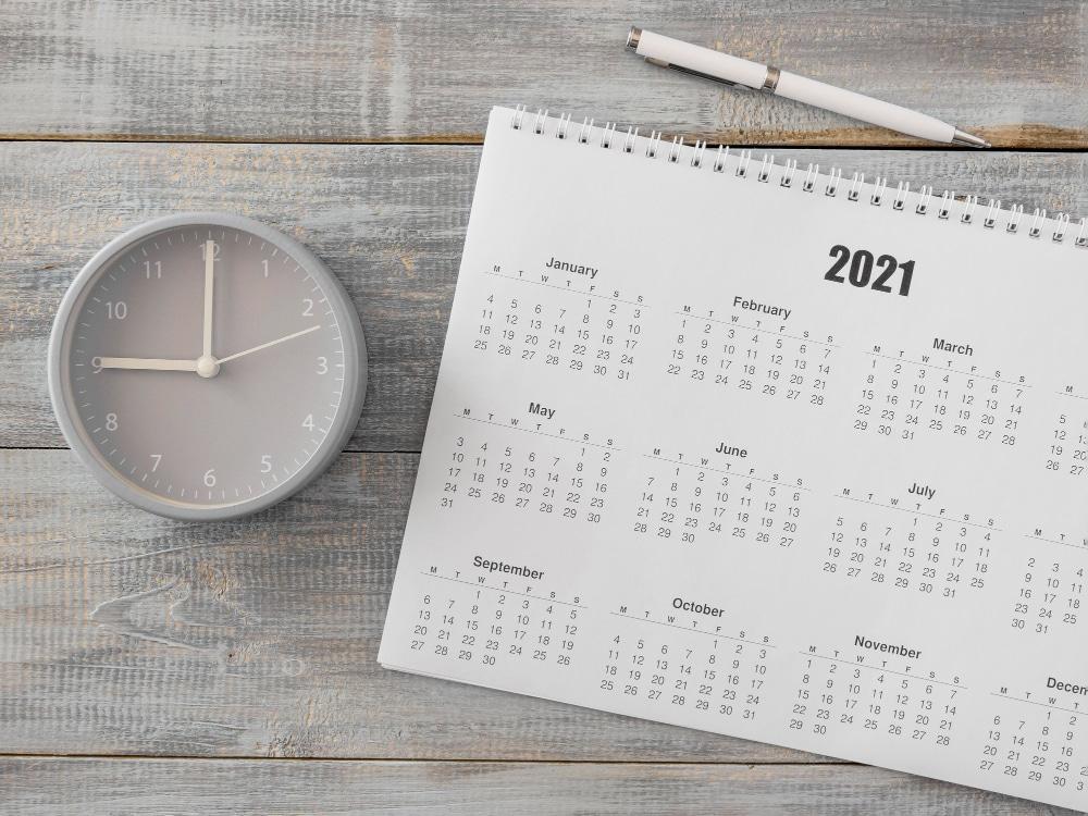 papel para calendário personalizado, com uma caneta e um relógio ao lado