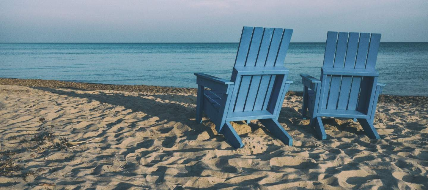 Two blue wooden chairs on a beach
