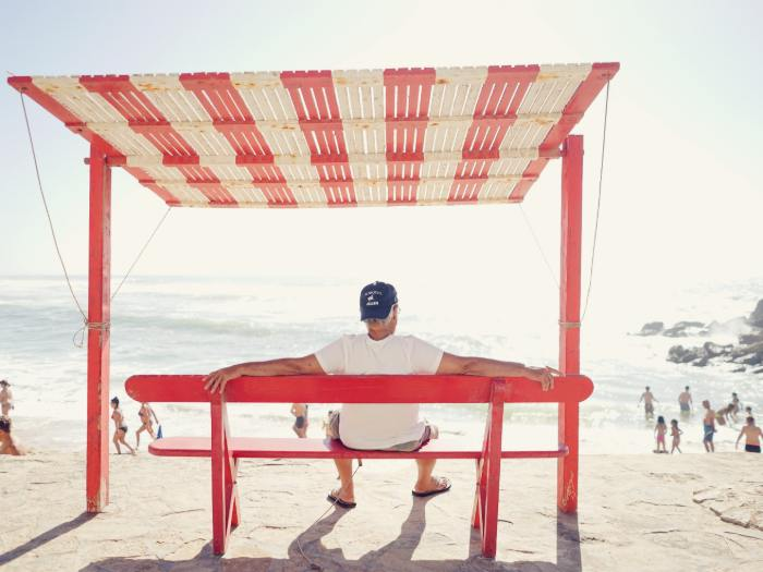 Man sitting on bench on a beach