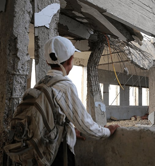 School student looking at his damaged school