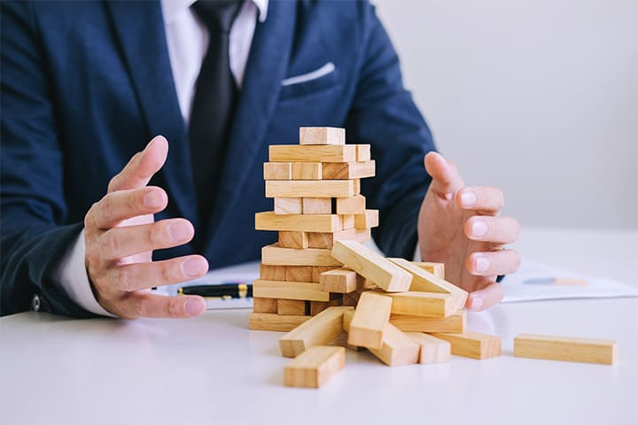 Business man with toppling blocks - property management mistakes metaphor