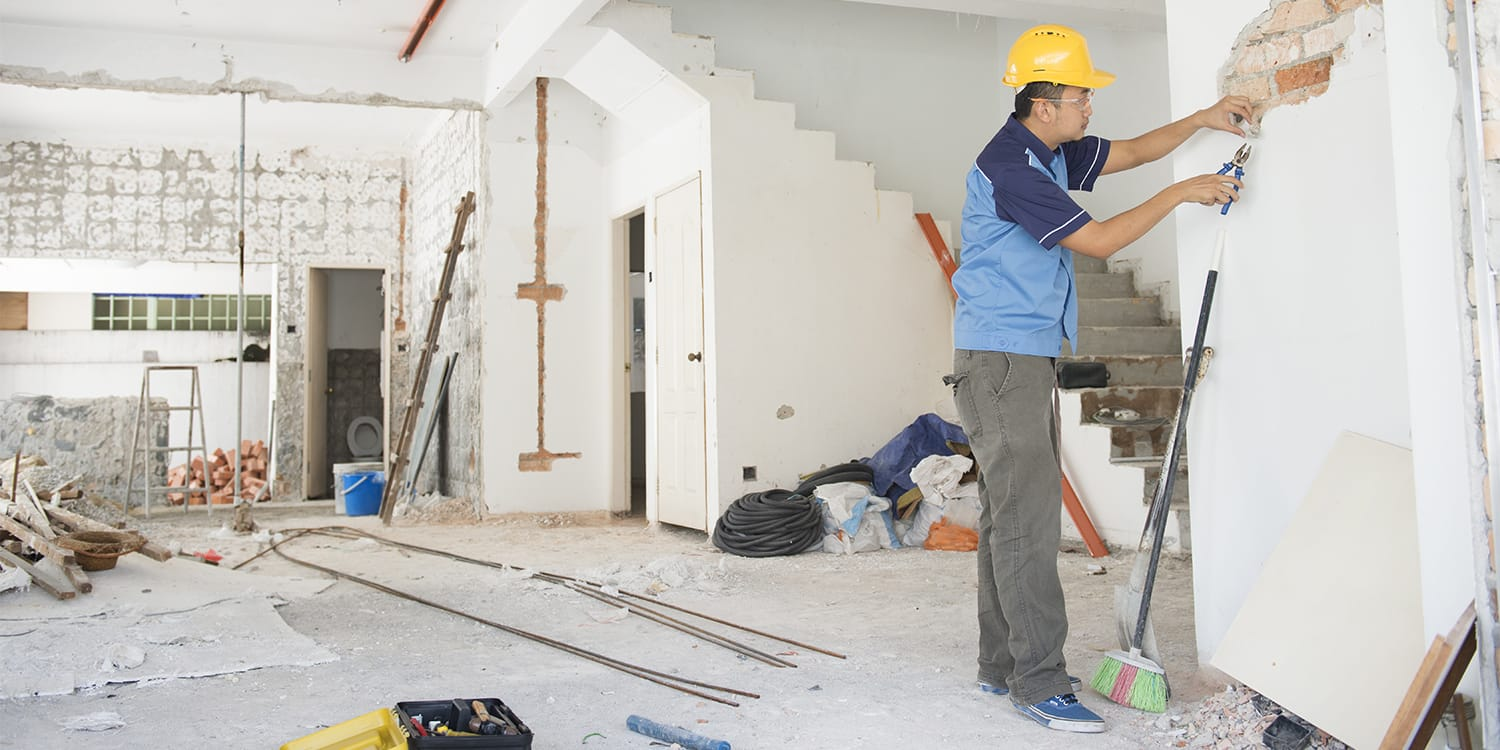 Asian man repairing house - First-time house flippers concept