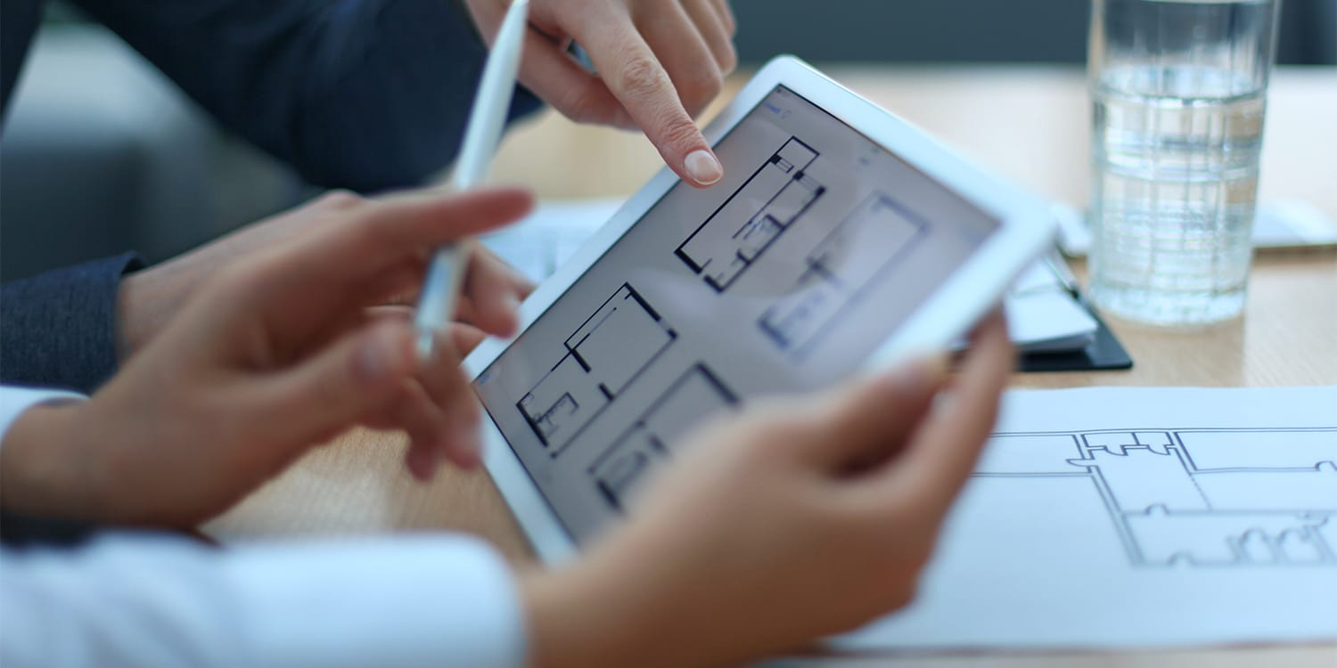 Property manager and landlord reviewing floor plans