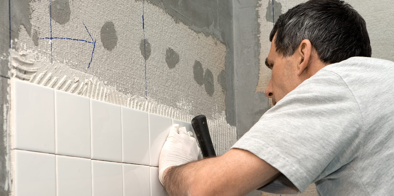 Handyman laying tile in a bathroom