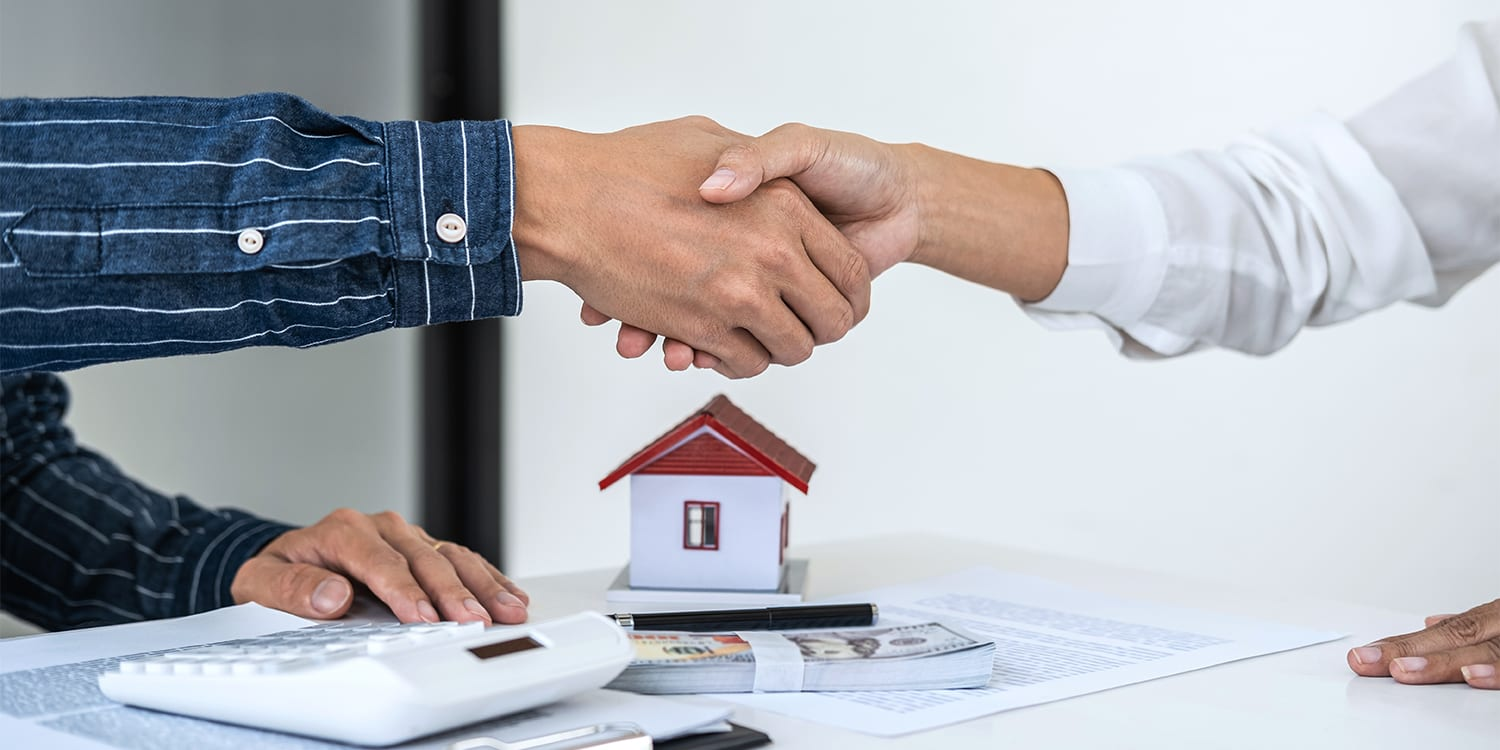 Real estate investor shaking hands with client after cash home sale agreement.