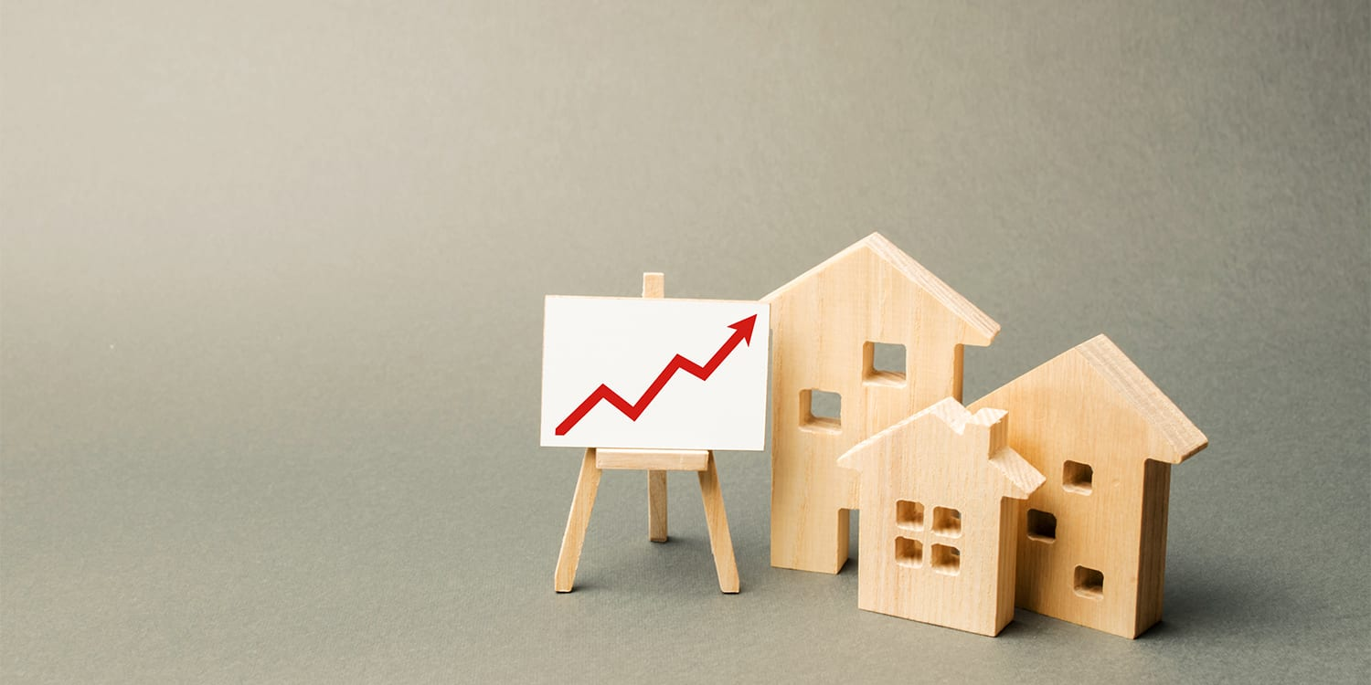 Wooden houses and chart to illustrate increased home selling price