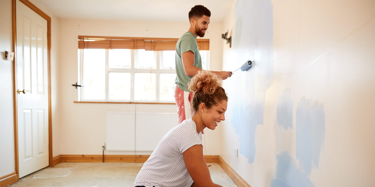 Couple painting and preparing to sell home