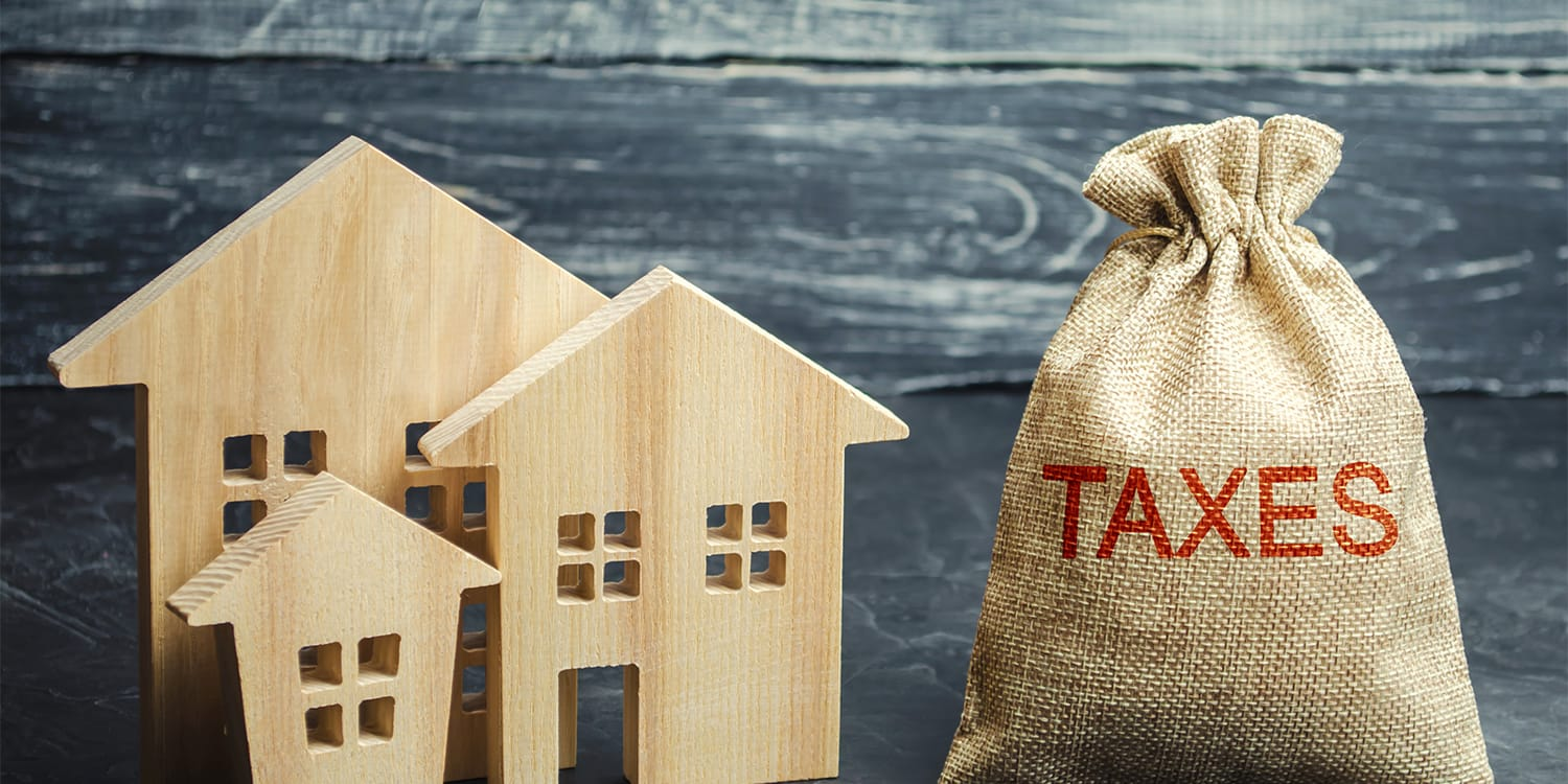 Conceptual image of property taxes dominating house