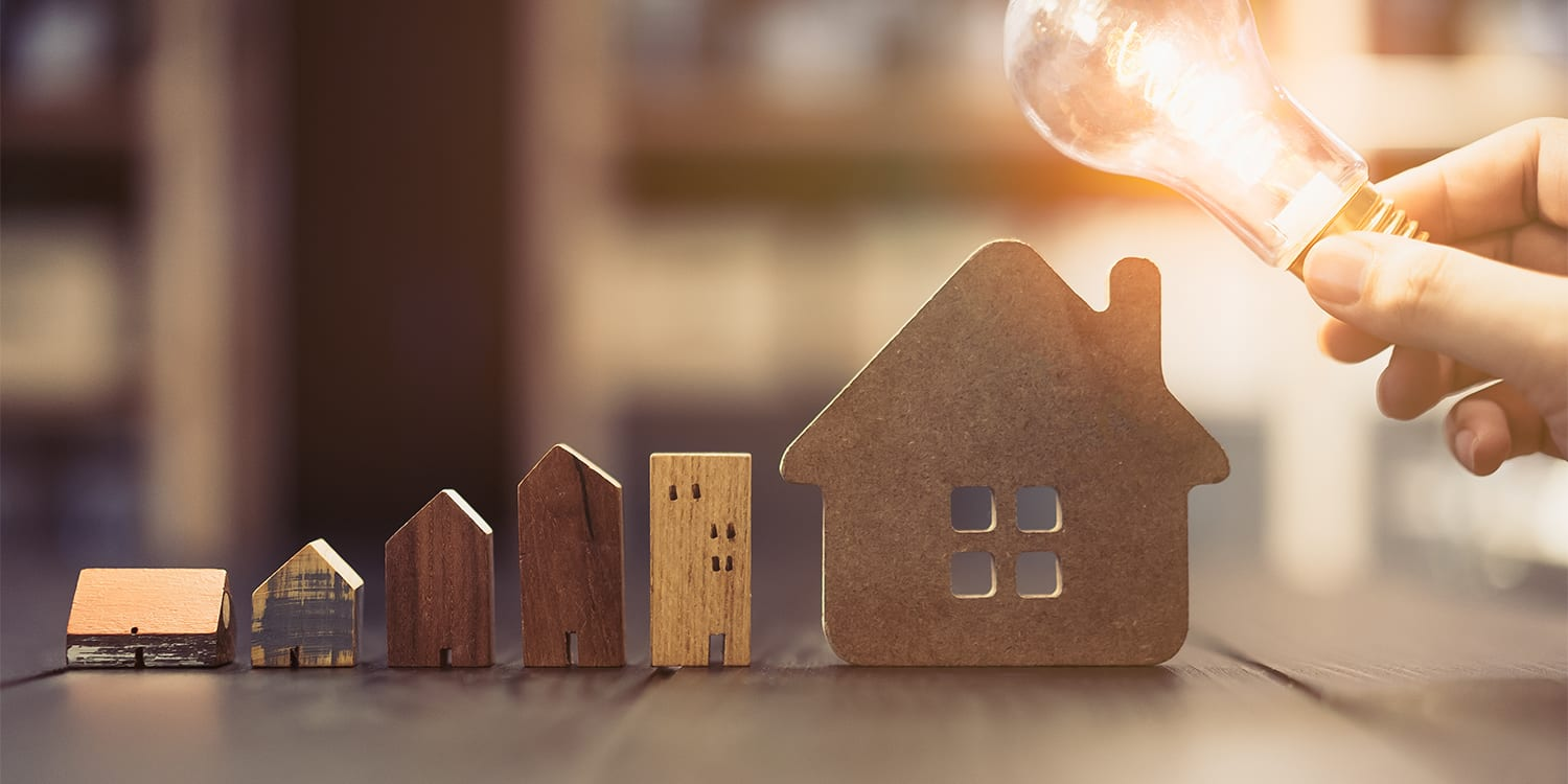 Wooden houses and lightbulb to represent real estate investment concept of buying probate properties