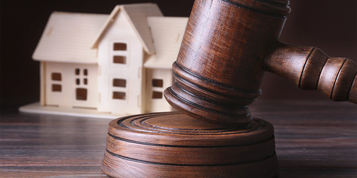 Foreclosure legal concept with gavel and wooden house