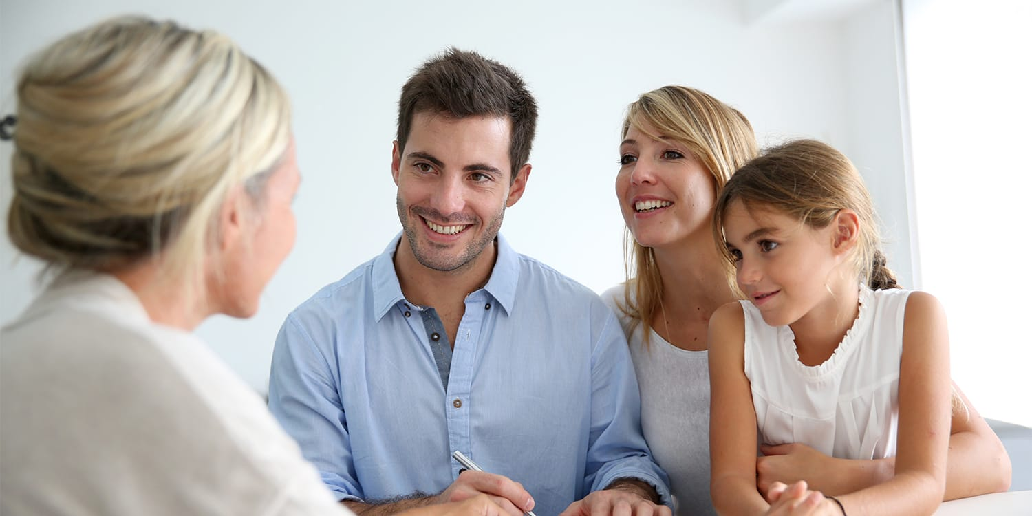 Realtor consulting with clients at desk.