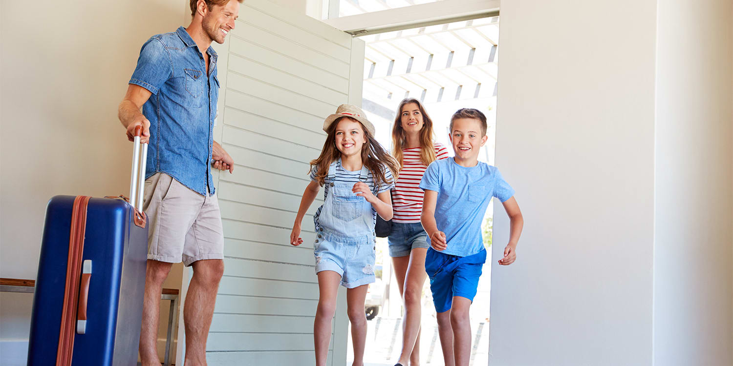 Happy family entering a vacation rental home.