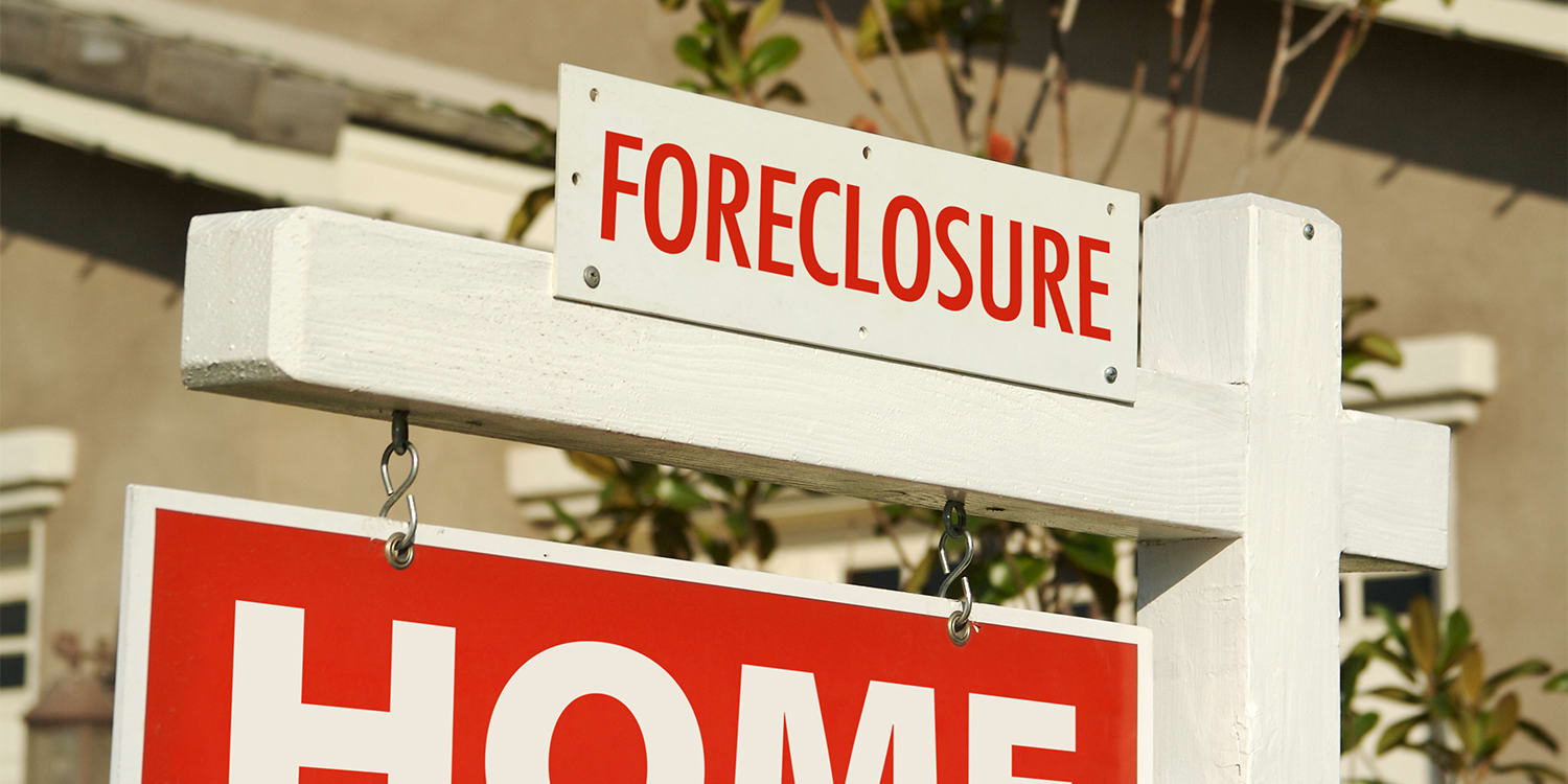 Signs of foreclosure in front of a house.