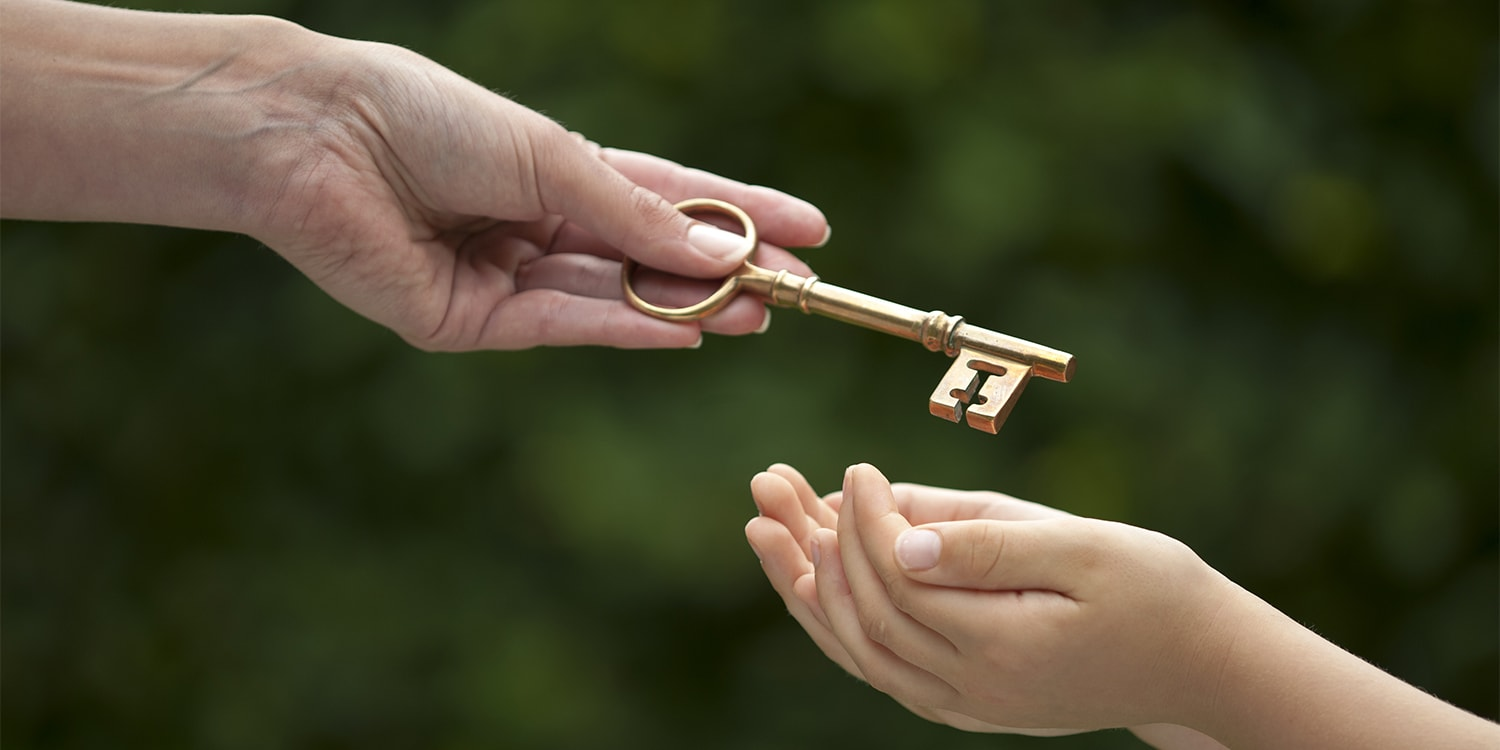 Mother handing key to daughter - inherited property concept
