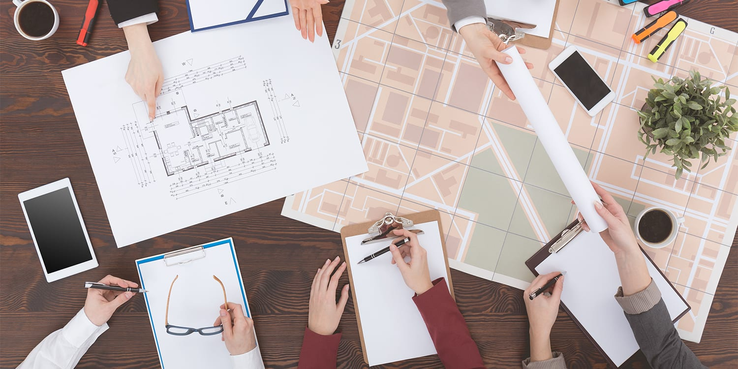 Real estate investors collaborating with plans
