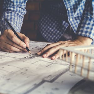 Man with blueprints - renovation budgeting concept