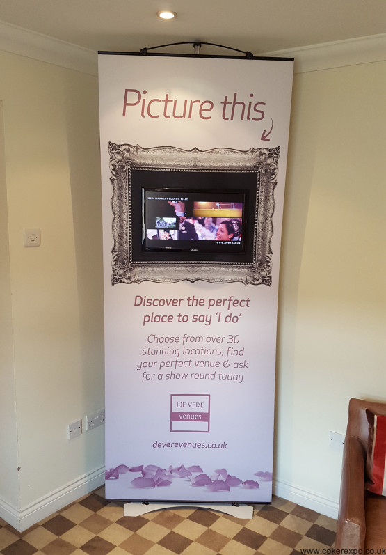 A twist banner stand with a Lcd screen mounted to it