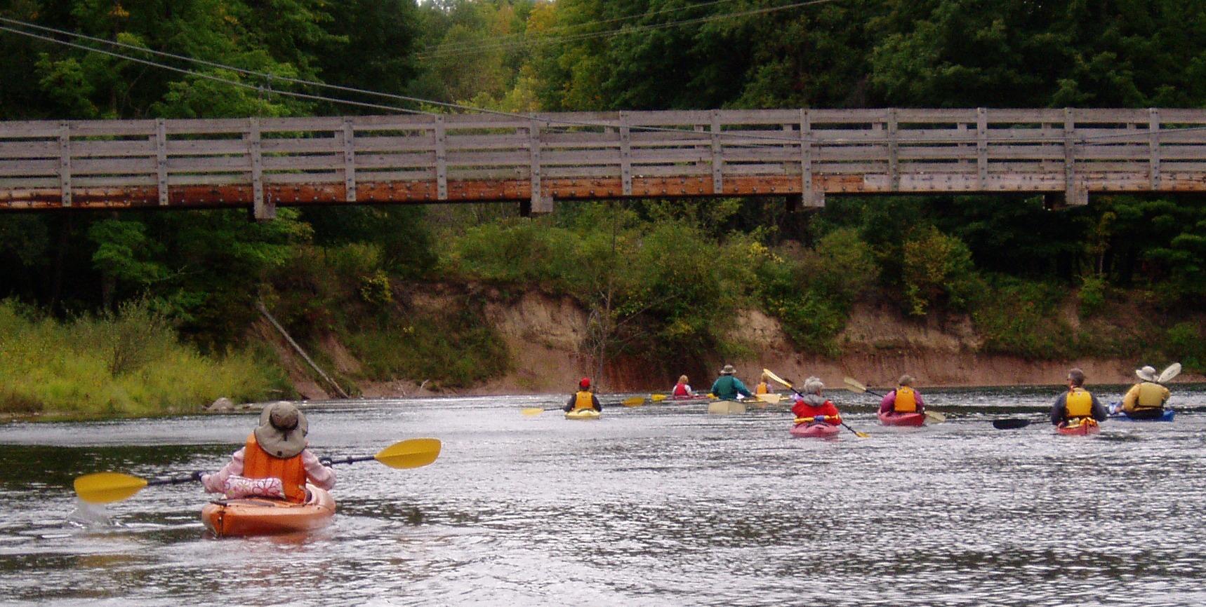 Kayakers paddiling below the suspension bridge on the big Manistee