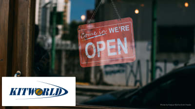 A sign in a shop window saying open with Kitworld logo