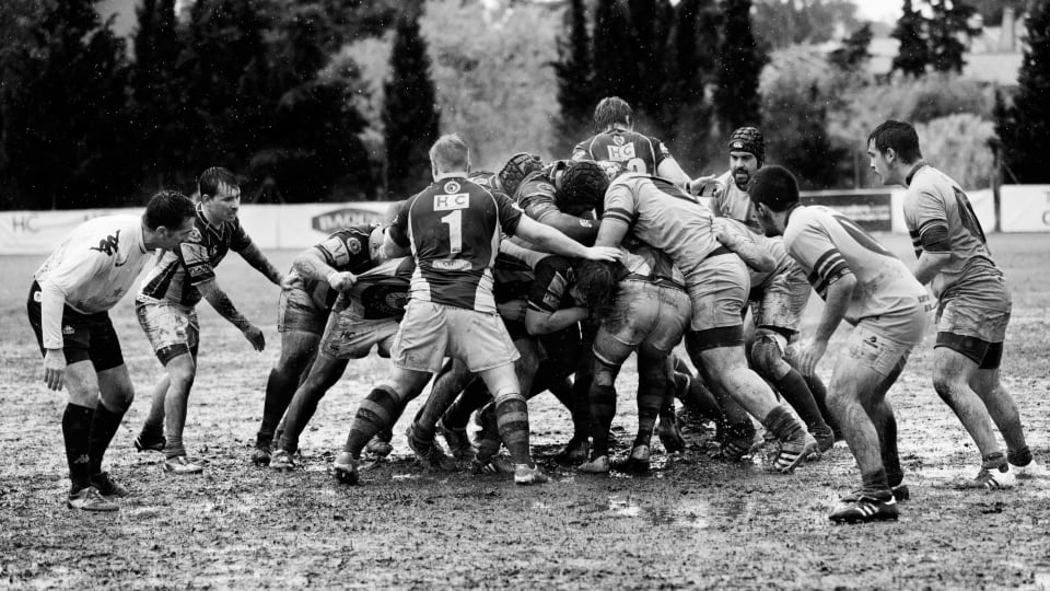 A rugby scrum played in the rain and mud taken in black and white