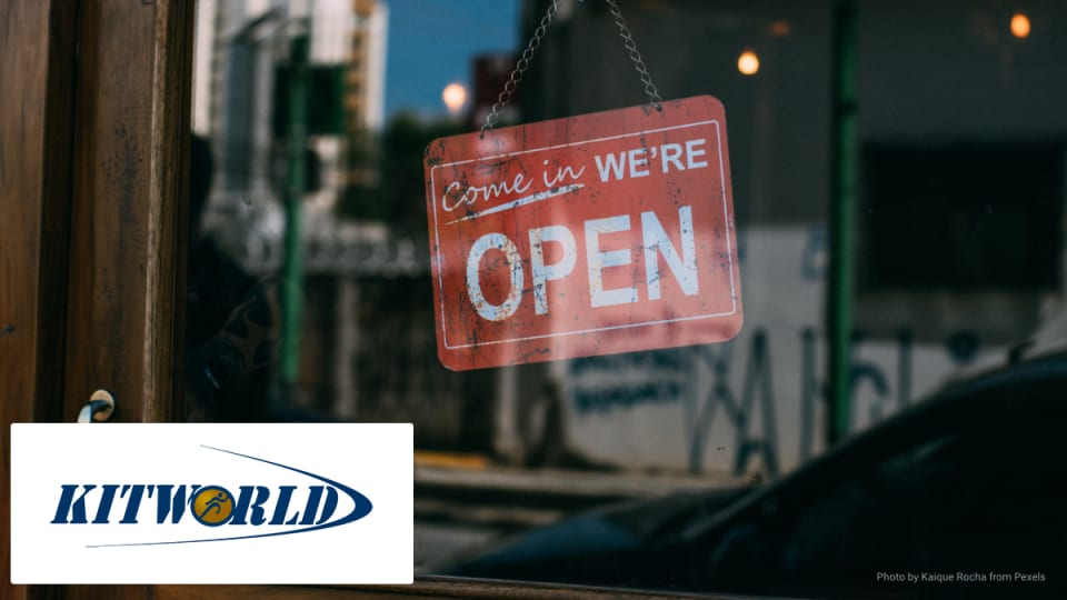 A sign in a shop window saying open with Kitworld logo.