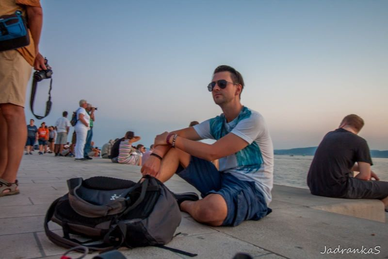 Jon sitting near the sea