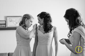 Bridesmaids adjusting dresses with pins