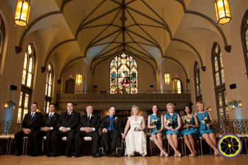 Seated portrait of groomsmen and bridesmaids alongside bride and groom in wheelchairs