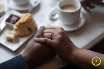 close-up photograph of hand holding, near a table with scones and tea, highlighting the woman's engagement ring