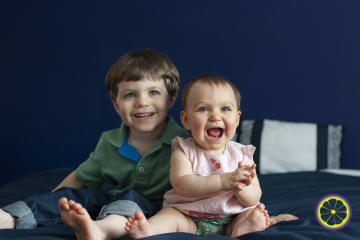 brother and sister smiling on bed in columbia mo